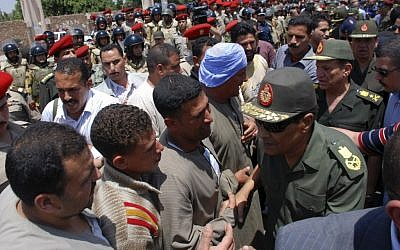 Field Marshal Hussein Tantawi, right, greets mourners at a military funeral for a commando killed in clashes with protesters in Cairo on Saturday (photo credit: AP Photo)