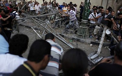 Egyptian protesters remove barbed wire blocking the road during a rally demanding the release of fellow activists (photo credit: AP/Nasser Nasser)