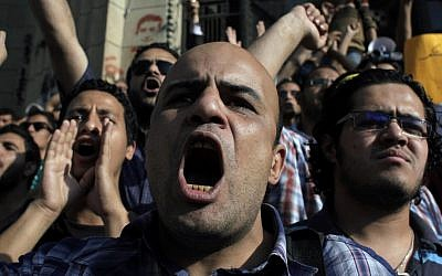 Egyptian protesters chant anti-military slogans during a rally demanding the release of fellow activists who were detained during a protest last Friday in front of the Ministry of Defense (photo credit: Nasser Nasser/AP)