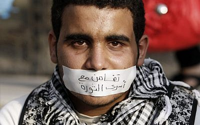 "An Egyptian man wearing a banner on his mouth that reads, ""with the revolutionary families,"" attends a demonstration in Cairo, on Wednesday (photo credit: AP/Fredrik Persson)"