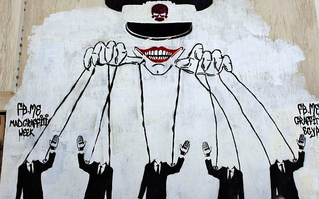Graffiti on a wall in Cairo depicts the ruling military council controlling the presidential elections as a puppet show. (photo credit: Nasser Nasser/AP)