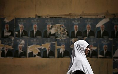 An Egyptian woman walks past defaced posters of Egyptian presidential candidate Ahmed Shafiq in Cairo (photo credit: AP Photo/Manu Brabo)