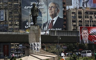 A statue of Nobel laureate Naguib Mahfouz with electoral advertisements for presidential candidates Amr Moussa, left, and Mohammed Morsi, right, in Cairo, Egypt. (photo credit: AP/Nasser Nasser)