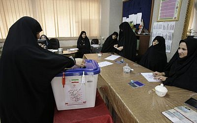 An Iranian woman casts her ballot for the parliamentary runoff elections, in a polling station, in Tehran, Iran, Friday. (photo credit: AP)