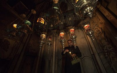 An Armenian Orthodox priest lights candles in the hanging oil lamps at the tomb of Jesus in the Holy Sepulchre church. (photo credit:AP/Dusan Vranic)