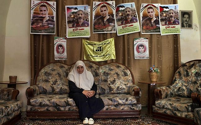 Dalal, mother of Mohammed al-Taj, sits underneath posters showing her son at their family house in the West Bank village of Tubas. (photo credit: AP/Bernat Armangue)
