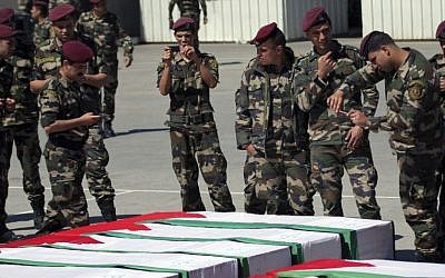 Members of the Palestinian security forces take pictures as they stand around coffins containing the remains of bodies of Palestinian terrorists transferred from Israel to the Palestinian Authority in 2012 (photo credit: AP/Mohammed Ballas)