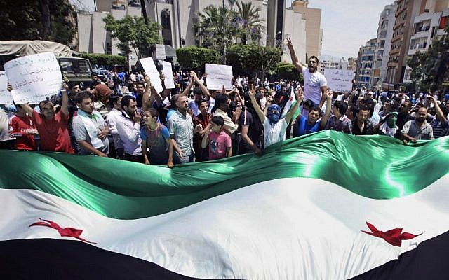Anti-Assad regime protesters wave a giant Syrian revolutionary flag during a demonstration in Beirut in May (photo credit: AP/Bilal Hussein)