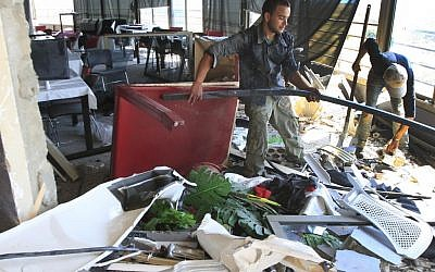 Workers remove debris from a south Lebanon restaurant which was bombed because it serves alcohol (photo credit: AP Photo/Mohammed Zaatari)