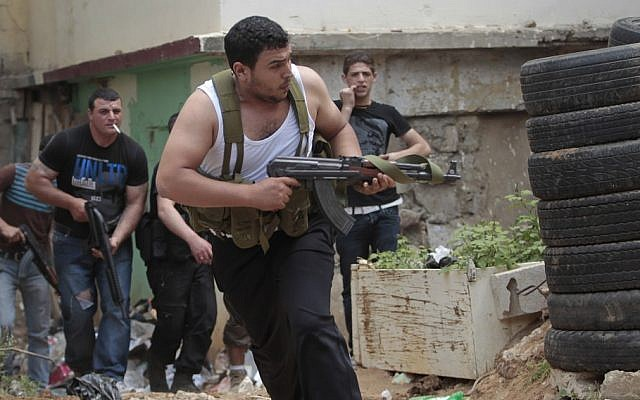 A Sunni gunman runs with his weapon during clashes in the northern port city of Tripoli, Lebanon, this month (photo credit: Hussein Malla/AP)