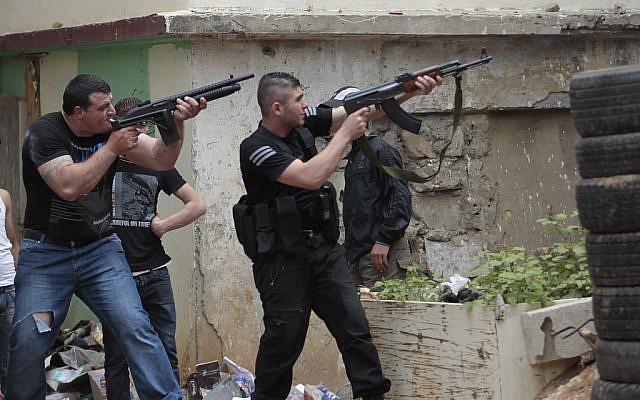 Sunni gunmen fire their rifles during clashes, in the northern port city of Tripoli, Lebanon, Sunday. (photo credit: AP/Hussein Malla)