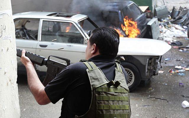 A Sunni gunman fires during running gun battles in the northern port city of Tripoli, Lebanon. (photo credit: AP/Hussein Malla)