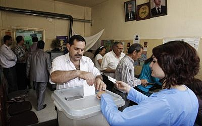A man casts his vote at a polling station during the parliamentary elections in Damascus on Monday. (photo credit: Muzaffar Salman/AP)