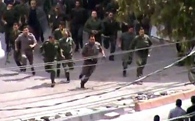 Police running toward a protest in Damascus, Syria, May 2012. The image is taken from an amateur video. AP cannot independently verify the photo. (photo credit: AP/Shaam News Network via AP video)