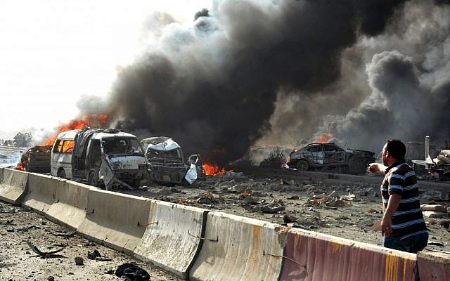 Flames and smoke rise from burned cars after two bombs exploded in Damascus, Syria, in early May (photo credit: AP/SANA)