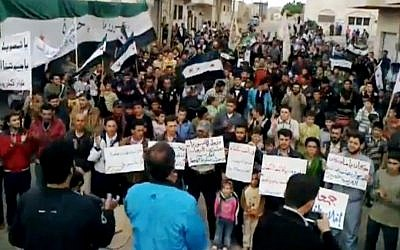 Syrians chanting anti-regime slogans during a demonstration in Idlib, north Syria, Sunday (photo credit: AP Photo/Shaam News Network via AP video)