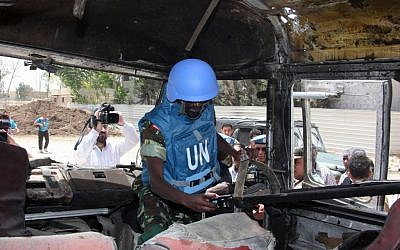A UN observer photographs a military bus damaged by a roadside bomb near Damascus on Wednesday (photo credit: AP/Bassem Tellawi)