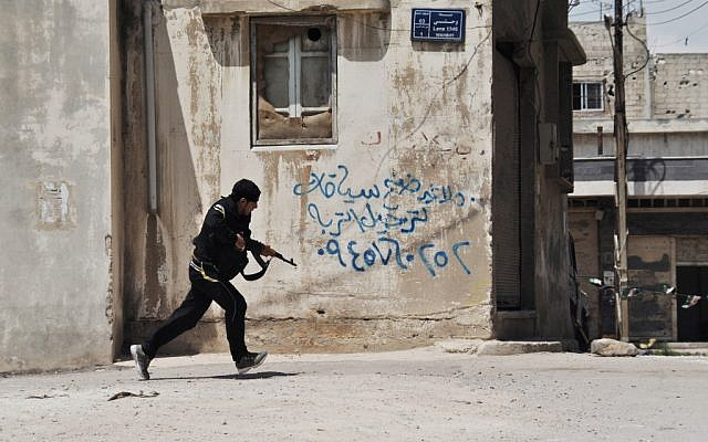 A Syrian opposition fighter runs for cover in Homs last month (photo credit: Fadi Zaidan/AP)