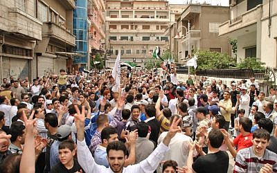 Syrians chant slogans during an opposition demonstration in Homs, Syria. The opposition is becoming increasingly divided over policies. (photo credit: AP)