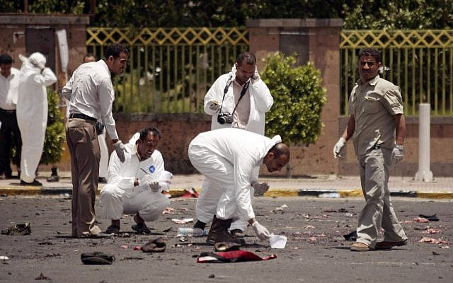 Forensic experts collect evidence at the site of the explosion in Sanaa, Yemen (photo credit: AP Photo/Hani Mohammed)