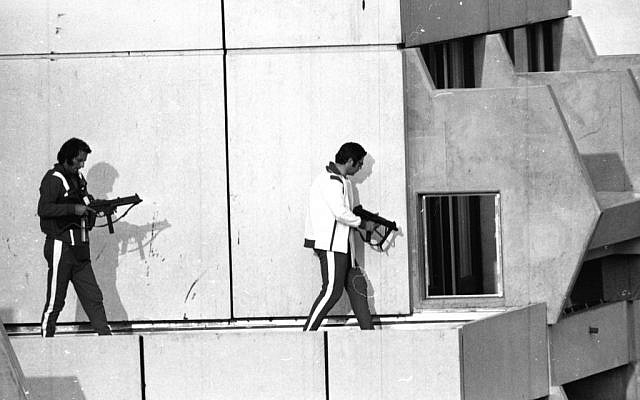 Two West German policemen, armed with submachine guns and wearing tracksuits, get into position on the roof of the building where armed Palestinian terrorists were holding Israel Olympic team members hostage, September 5, 1972 (photo credit:AP)