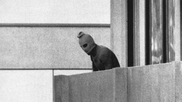 A member of the Arab Commando group which seized members of the Israeli Olympic Team at their quarters at the Munich Olympic Village appears with a hood over his face on the balcony of the village building where the commandos held several members of the Israeli team hostage, on Sept. 5, 1972 (photo credit: AP Photo/Kurt Strumpf, File)