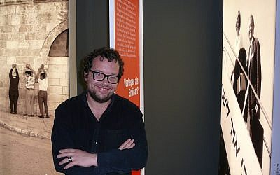 Curator Dmitrij Belkin next to a photo of Axel and Friede Springer looking down from an El-Al-airplane. (Igal Avidan)