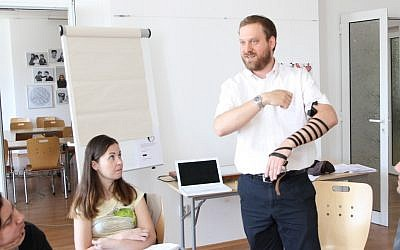 Rabbi Josh Ahrens demonstrates how to put on tefillin during a conversion course at the Sofia JCC in Bulgaria. (Dianna Cahn)