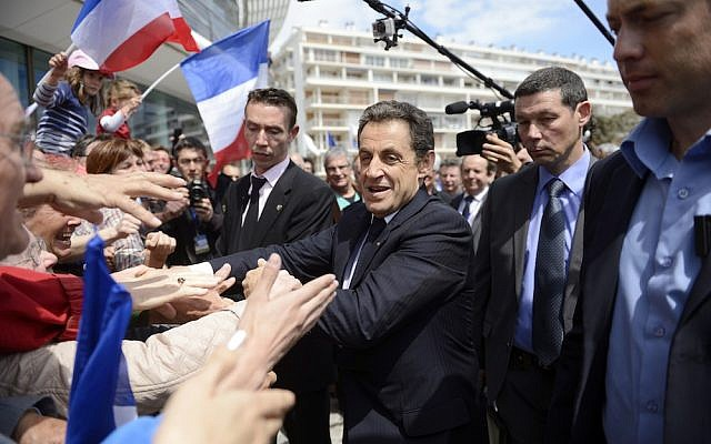 France's president and conservative candidate for re-election in 2012, Nicolas Sarkozy, shakes hands with crowds of supporters (photo credit: AP/Eric Feferberg)