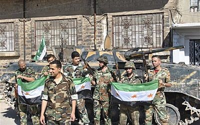 Syrian army soldiers hold the Syrian revolution flags shortly after they defected and joined the rebels, in Homs province on Saturday (AP/Fadi Zaidan)