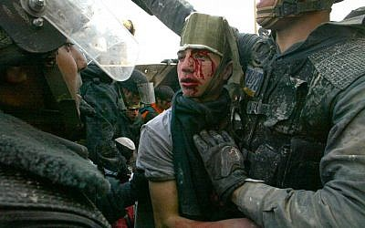 An injured settler is arrested by border policemen during clashes in the West Bank outpost of Amona on January 1, 2006. (photo credit: Olivier Fitoussi/Flash90)