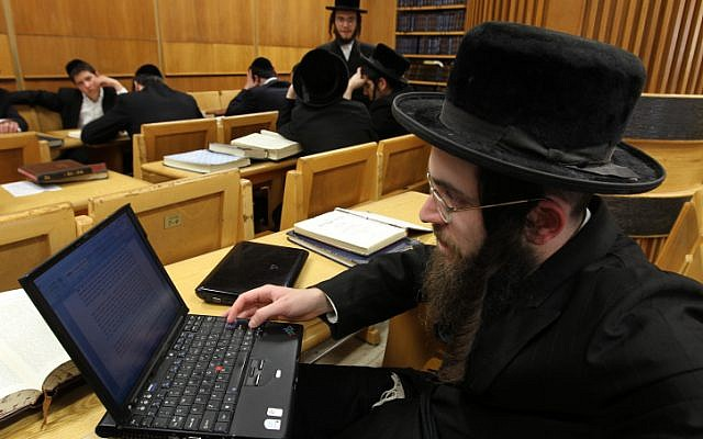 An ultra-Orthodox man studying religious texts with a computer at a Yeshiva in Jerusalem (photo credit: Nati Shohat/Flash90)