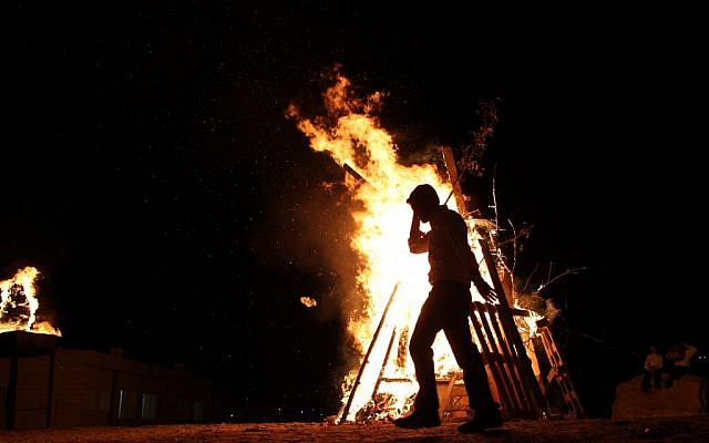 A child adds wood to a Lag Ba'omer bonfire in Betar Illit on Wednesday night. (photo credit: Nati Shohat/Flash90)