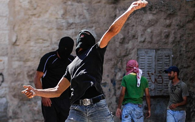 Illustrative photo of Palestinians throwing stones at Israeli policemen during protests in East Jerusalem (photo credit: Noam Moskowitz/Flash90)