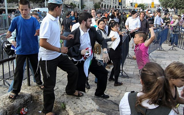 A young Arab boy fights with a Jewish man during a march celebrating Jerusalem Day (photo credit: Nati Shohat/Flash90)