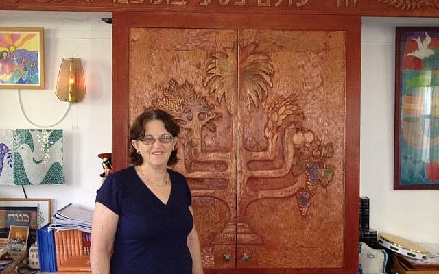 Rabbi Miri Gold in front of the 'Aron Kodesh' at Kibbutz Gezer's Kehilat Birkat Shalom (photo credit: Amanda Borschel-Dan/Times of Israel)