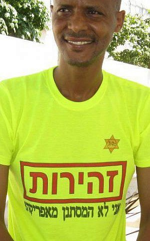 Elias Inbram sports a shirt of his own design that reads in Hebrew 'Caution I am not an African infiltrator' (photo credit: Facebook)