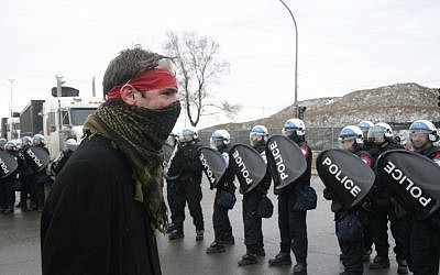 A protester facing off against police in Montreal in March. (illustrative photo: CC-BY Socialist Canada, Socialist Quebec, Flickr)