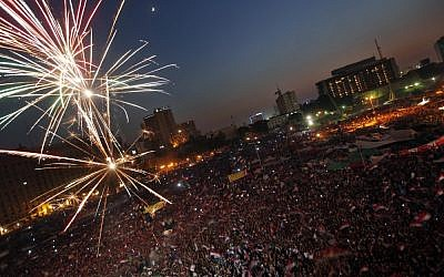 Fireworks illuminate Tahrir Square in Cairo, Egypt, as Egyptians gather to celebrate Mohammed Morsi's presidential win Sunday, June 24, 2012. (photo credit: AP/Khalil Hamra)