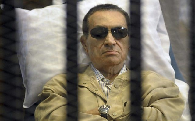 Egypt's ex-President Hosni Mubarak lies on a gurney inside a barred cage in the police academy courthouse in Cairo, Egypt earlier this month. (photo credit: AP)