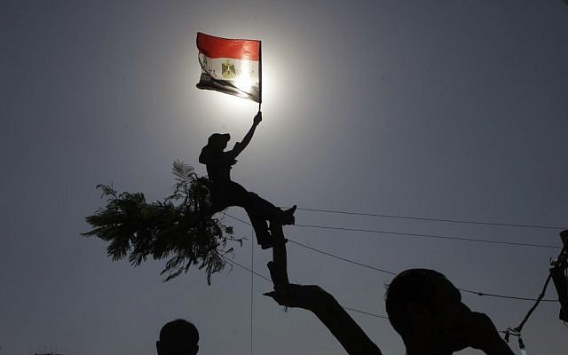 An Egyptian protester waves the national flag in Tahrir Square in Cairo (photo credit: Amr Nabil/AP)