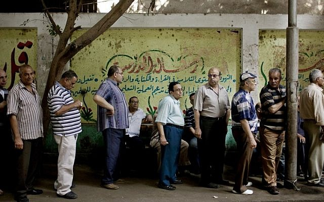 Egyptian men line up to vote at a polling station in Cairo on Sunday. (photo credit: Pete Muller/AP)