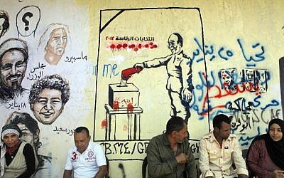 Egyptians sit in front of graffiti showing faces of people killed in the 2011 revolution, right, and the head of the Supreme Council of the Armed Forces, Field Marshal Hussein Tantawi, casting his vote, center, in Tahrir Square in Cairo, Egypt, Friday (photo credit: AP/Amr Nabil)