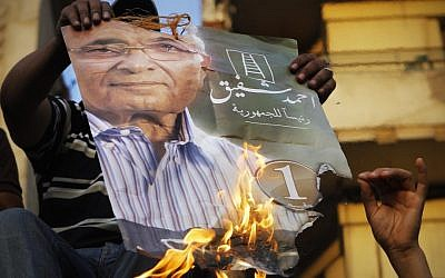Supporters of the Muslim Brotherhood's candidate Mohammed Morsi burn one of Ahmed Shafiq's election posters in Tahrir Square on Tuesday. (photo credit: Amr Nabil/AP)