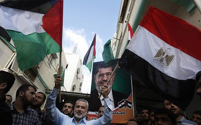 Hamas Prime Minister Ismail Haniyeh waves the Palestinian and Egyptian flags in Gaza City in June, 2012. (photo credit: Hatem Moussa/AP)