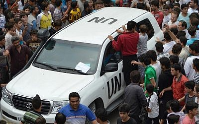 Syrians gather around a UN observers vehicle during a demonstration in northern Syria last week. (photo credit: Edlib News Network ENN/AP)