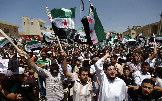 Syrians attend an anti-Bashar Assad protest after Friday prayers on the outskirts of Idlib, Syria, Friday (photo credit: AP)