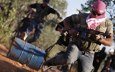 As the struggle to oust Syrian President Bashar Assad continues, Free Syrian Army members train with their weapons on the outskirts of Idlib, Syria, June 9 (photo credit: AP)