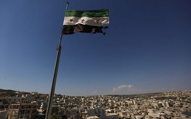 A Syrian revolutionary flag waves on top of a building on the outskirts of Aleppo, Syria, on Tuesday (photo credit:AP)