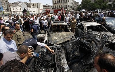 Syrians inspect burned cars at the site of a blast in the capital city, Damascus, Thursday. Opposition groups state Thursday was one of the bloodiest days since the Syrian uprising against President Basher Assad began. (photo credit: Muzaffar Salman/AP)